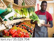Salesman offering green onions. Стоковое фото, фотограф Яков Филимонов / Фотобанк Лори