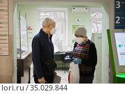 Пожилые пациенты в поликлинике в масках. Редакционное фото, фотограф Victoria Demidova / Фотобанк Лори