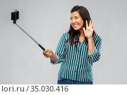 happy asian woman taking selfie and waving hand. Стоковое фото, фотограф Syda Productions / Фотобанк Лори