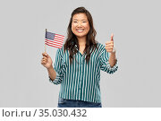 asian woman with flag of america showing thumbs up. Стоковое фото, фотограф Syda Productions / Фотобанк Лори
