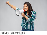 happy smiling asian woman speaking to megaphone. Стоковое фото, фотограф Syda Productions / Фотобанк Лори