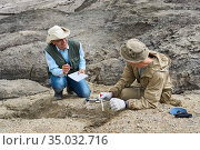 Two paleontologists in the desert discuss the find and take notes in a field notebook. Стоковое фото, фотограф Евгений Харитонов / Фотобанк Лори