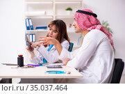 Young arab businessman visiting caucasian female doctor. Стоковое фото, фотограф Elnur / Фотобанк Лори