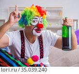 Drunk clown celebrating having a party at home. Стоковое фото, фотограф Elnur / Фотобанк Лори