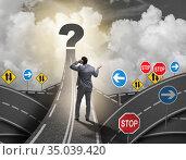 Businessman in uncertainty concept on road intersection crossroa. Стоковое фото, фотограф Elnur / Фотобанк Лори