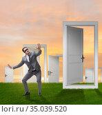 Confused businessman in front of doors. Стоковое фото, фотограф Elnur / Фотобанк Лори