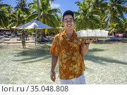 A waiter serves cocktails in Taha'a island resort, French Polynesia... Редакционное фото, фотограф Sergi Reboredo / age Fotostock / Фотобанк Лори