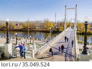 Ural river embankment, Orenburg, Russia - October, 18, 2020: Citizens walking on the pedestrian bridge. Редакционное фото, фотограф Вадим Орлов / Фотобанк Лори