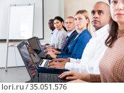 Side view of latin american businessman with laptop during business training. Стоковое фото, фотограф Яков Филимонов / Фотобанк Лори