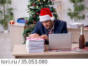Young male employee celebrating new year in the office. Стоковое фото, фотограф Elnur / Фотобанк Лори