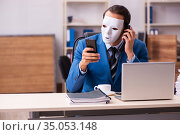 Young male employee wearing masks in the office. Стоковое фото, фотограф Elnur / Фотобанк Лори