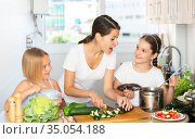 Happy kids with mom prepare vegetable salad in the kitchen. Стоковое фото, фотограф Яков Филимонов / Фотобанк Лори