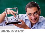 Young male teacher physicist in front of blackboard. Стоковое фото, фотограф Elnur / Фотобанк Лори
