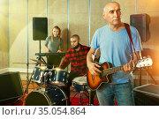 Rehearsal of music group. Band leader playing guitar and singing. Стоковое фото, фотограф Яков Филимонов / Фотобанк Лори