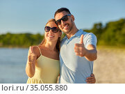 happy couple showing thumbs up on summer beach. Стоковое фото, фотограф Syda Productions / Фотобанк Лори