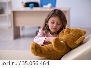 Small girl holding bear toy waiting for doctor in the clinic. Стоковое фото, фотограф Elnur / Фотобанк Лори