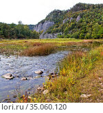 Ural. Water autumn landscape. A shallow fast mountain river with a rocky bottom. In the background there are rocks overgrown with forest. Стоковое фото, фотограф Акиньшин Владимир / Фотобанк Лори
