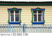 Beautiful windows with carved platbands on the facade of a residential building. Стоковое фото, фотограф Акиньшин Владимир / Фотобанк Лори
