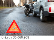Warning triangle sign standing on a distance from road collision with motorbike and car. Стоковое фото, фотограф Кекяляйнен Андрей / Фотобанк Лори