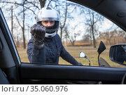 Angry motorcyclist knocking with fist in glove in car side window, view from inside. Стоковое фото, фотограф Кекяляйнен Андрей / Фотобанк Лори