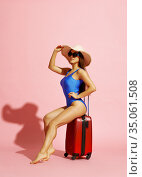 Woman in swimsuit and hat poses with suitbag. Стоковое фото, фотограф Tryapitsyn Sergiy / Фотобанк Лори