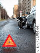 Triangular safety reflector is on asphalt road, sign is on the distance of car and motorcycle crash. Стоковое фото, фотограф Кекяляйнен Андрей / Фотобанк Лори