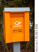 Orange postbox with old logotype of Estonian Post is on stand in countryside still. From the 2014 it has adopted new logo and name the Omniva. Estonia (2018 год). Редакционное фото, фотограф Кекяляйнен Андрей / Фотобанк Лори
