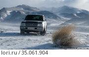 Video of suv car Toyota Land Cruiser 100 in Altai highlands mountains in winter blizzard and snowstorm. Редакционное видео, видеограф Serg Zastavkin / Фотобанк Лори