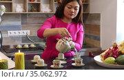Cute Vietnamese woman prepares traditional Vietnamese tea at the bar of a cafe. Стоковое видео, видеограф Алексей Кузнецов / Фотобанк Лори