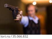 Smallbore sporting pistol in hand of man training in shooting range. Стоковое фото, фотограф Яков Филимонов / Фотобанк Лори