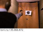 Man practicing firearms target shooting in pistol range. Стоковое фото, фотограф Яков Филимонов / Фотобанк Лори