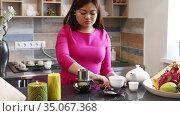 Middle aged Vietnamese woman prepares traditional Vietnamese coffee at the bar of a cafe. Стоковое видео, видеограф Алексей Кузнецов / Фотобанк Лори