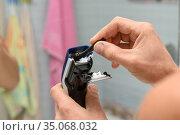 Мужчина проводит очистку машинки для стрижки волос с помощью щеточки. Стоковое фото, фотограф Иванов Алексей / Фотобанк Лори