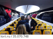 Schoenefeld, Germany, people in a Ryanair cabin stow their hand luggage before departure (2019 год). Редакционное фото, агентство Caro Photoagency / Фотобанк Лори