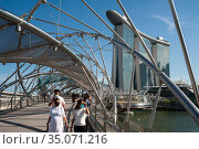 Singapore, Republic of Singapore, People with mouthguards crossing the Helix Bridge in Marina Bay. Редакционное фото, агентство Caro Photoagency / Фотобанк Лори