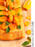 Orange Pound Cake flavored with freshly squeezed orange juice and zest decorated with dried apricots, mint and almonds. Стоковое фото, фотограф Nataliia Zhekova / Фотобанк Лори