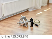 dumbbells, skipping rope and bottle on floor. Стоковое фото, фотограф Syda Productions / Фотобанк Лори