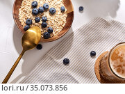 oatmeal with blueberries, spoon and coffee. Стоковое фото, фотограф Syda Productions / Фотобанк Лори