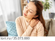 asian woman suffering from ache in neck at home. Стоковое фото, фотограф Syda Productions / Фотобанк Лори