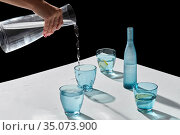hand pouring water to glasses with lemon and ice. Стоковое фото, фотограф Syda Productions / Фотобанк Лори