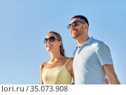 happy couple in sunglasses hugging over blue sky. Стоковое фото, фотограф Syda Productions / Фотобанк Лори