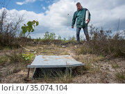 Pitfall trap used for weekly trapping of Ground beetles (Carabidae), researcher approaching in background. Long-term monitoring. has revealed a 72 percent... Стоковое фото, фотограф Edwin Giesbers / Nature Picture Library / Фотобанк Лори