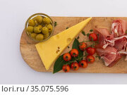 Olives, cheese, ham and cherry tomatoes on wooden board on white background. Стоковое фото, агентство Wavebreak Media / Фотобанк Лори