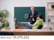 Aged physics teacher and male student in the classroom. Стоковое фото, фотограф Elnur / Фотобанк Лори
