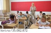Friendly female teacher working with tweenager pupils in classroom at primary school. Стоковое видео, видеограф Яков Филимонов / Фотобанк Лори