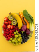 High angle view of bowl of banana, berries, grapes and baby aubergines. Стоковое фото, агентство Wavebreak Media / Фотобанк Лори