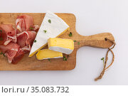 Cheese and ham on wooden board on white background. Стоковое фото, агентство Wavebreak Media / Фотобанк Лори