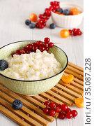 Легкий завтрак с творогом. Домашний зерненый творог с ягодами на белом деревянном столе. Стоковое фото, фотограф ирина реброва / Фотобанк Лори