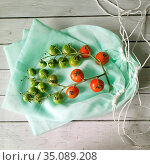 Reusable bag with fresh tomatoes cherry on white wood table background. Стоковое фото, фотограф Мария Сибатрова / Фотобанк Лори