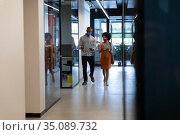 Diverse businessman and businesswoman wearing face masks checking documents in office. Стоковое фото, агентство Wavebreak Media / Фотобанк Лори